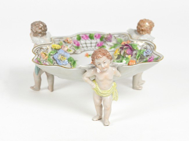 6: A SHALLOW DRESDEN BOWL SUPPORTED BY THREE CHERUB FIG
