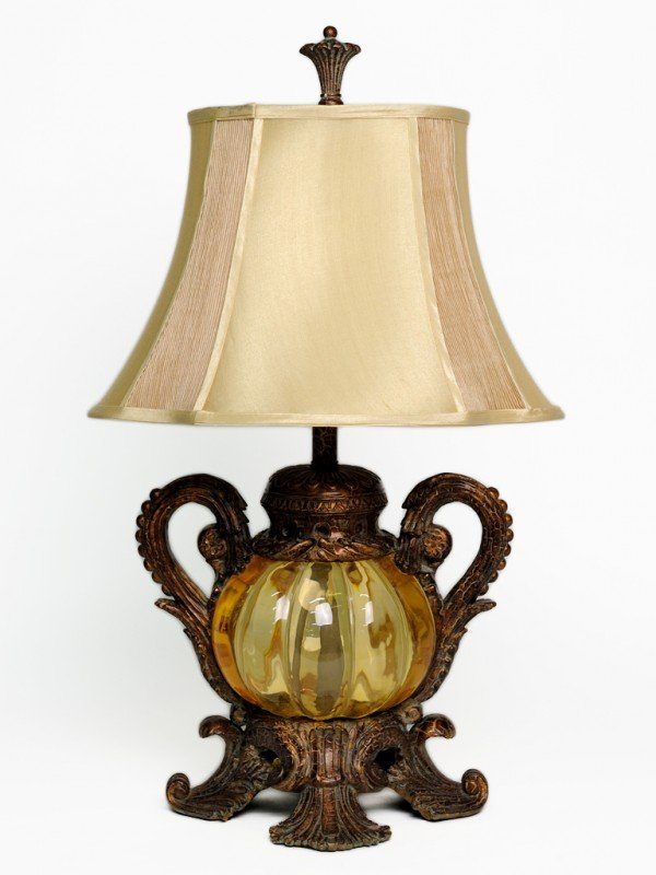 15: AN AMBER GLASS BELLIED TABLE LAMP ENCASED IN A HIGH