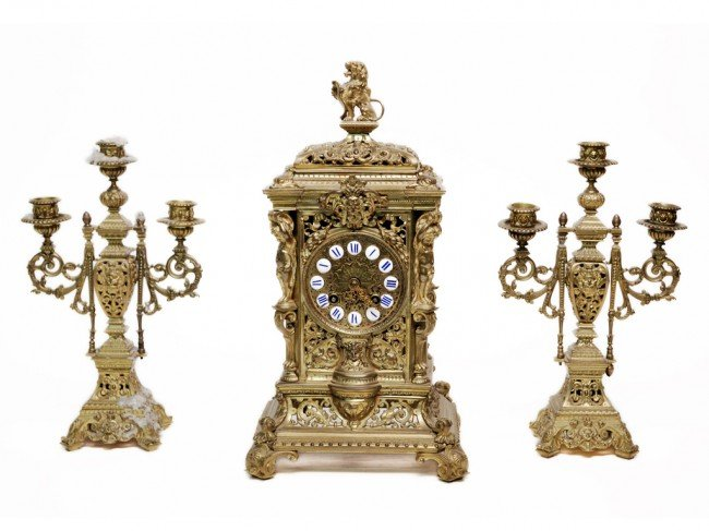 18: A THREE PIECE BRASS CLOCK SET INCLUDING TWO THREE L