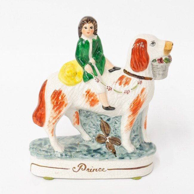 19: A STAFFORDSHIRE PORCELAIN FIGURE OF A BOY ON A DOG