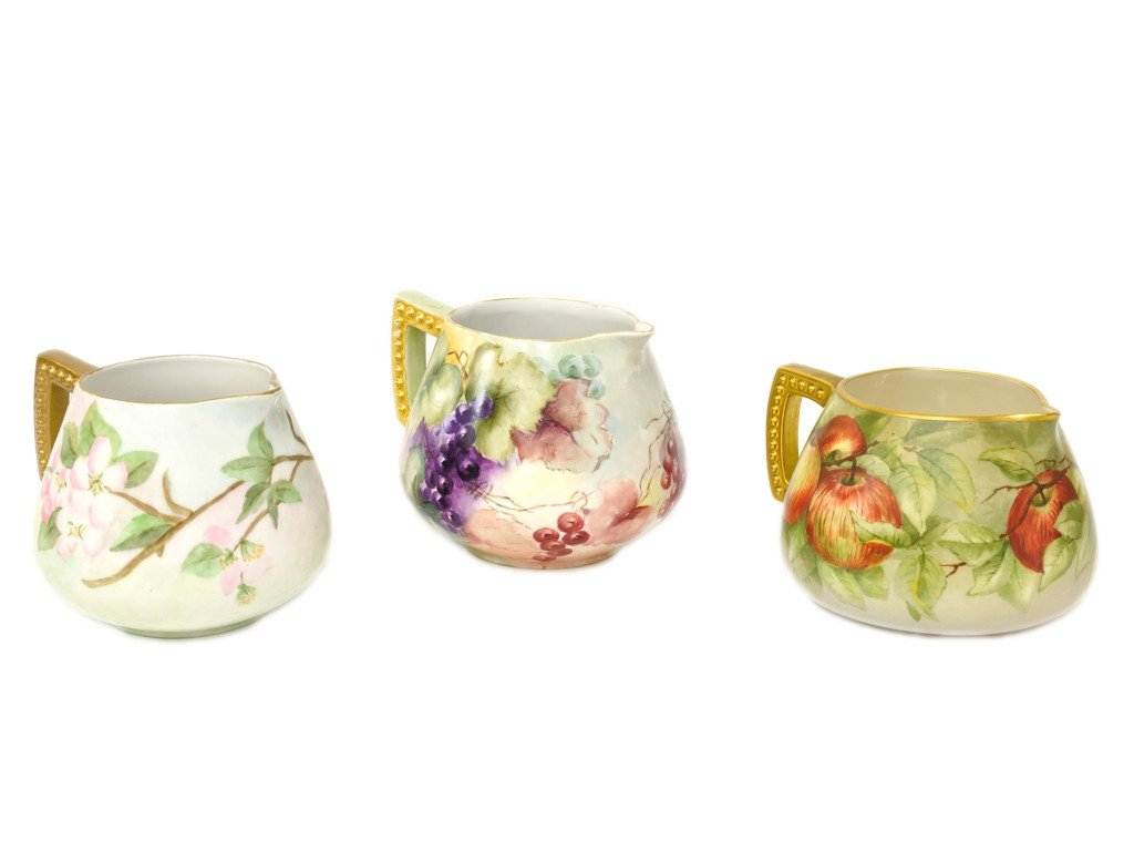 15: THREE HAND PAINTED AND GILT DECORATED PITCHERS, Ear