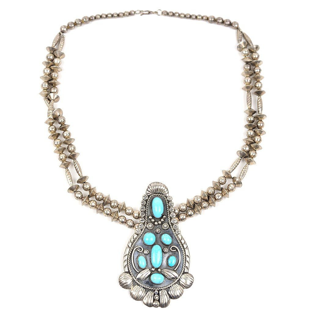 11: A SEVEN STONE TURQUOISE AND STERLING SILVER BEAR CL