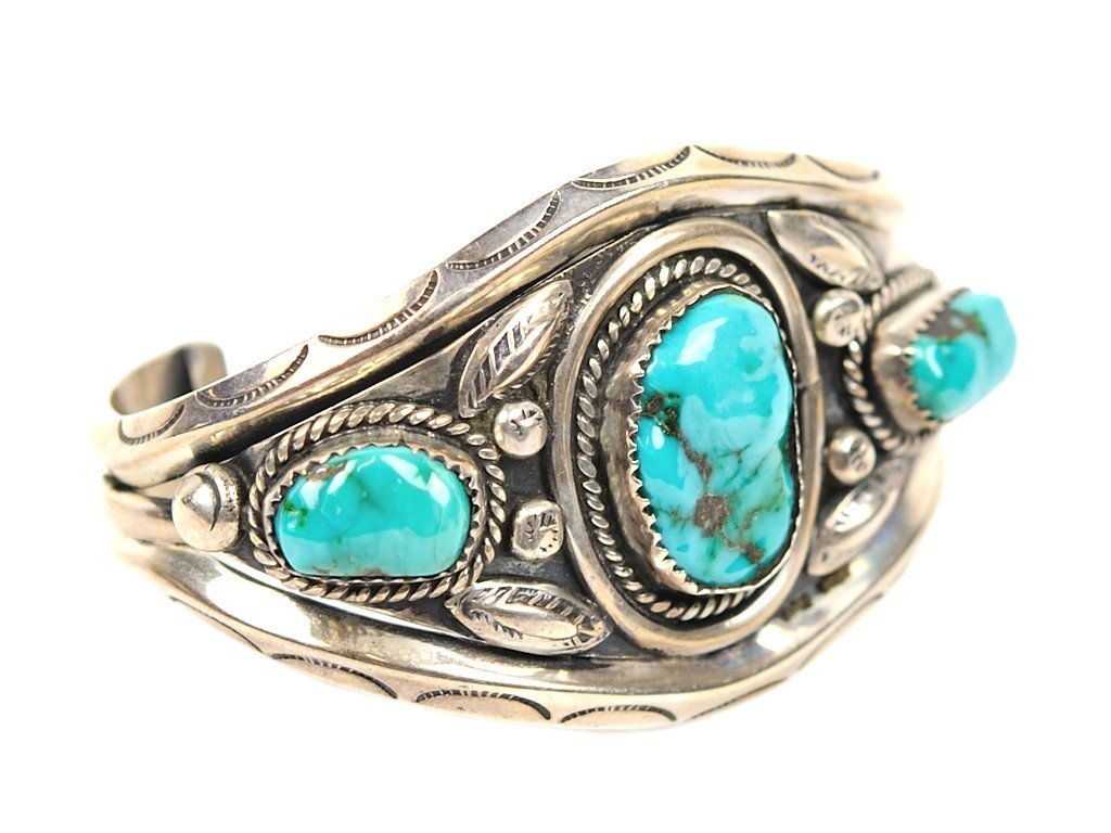 12: A THREE STONE TURQUOISE AND STERLING SILVER CUFF BR