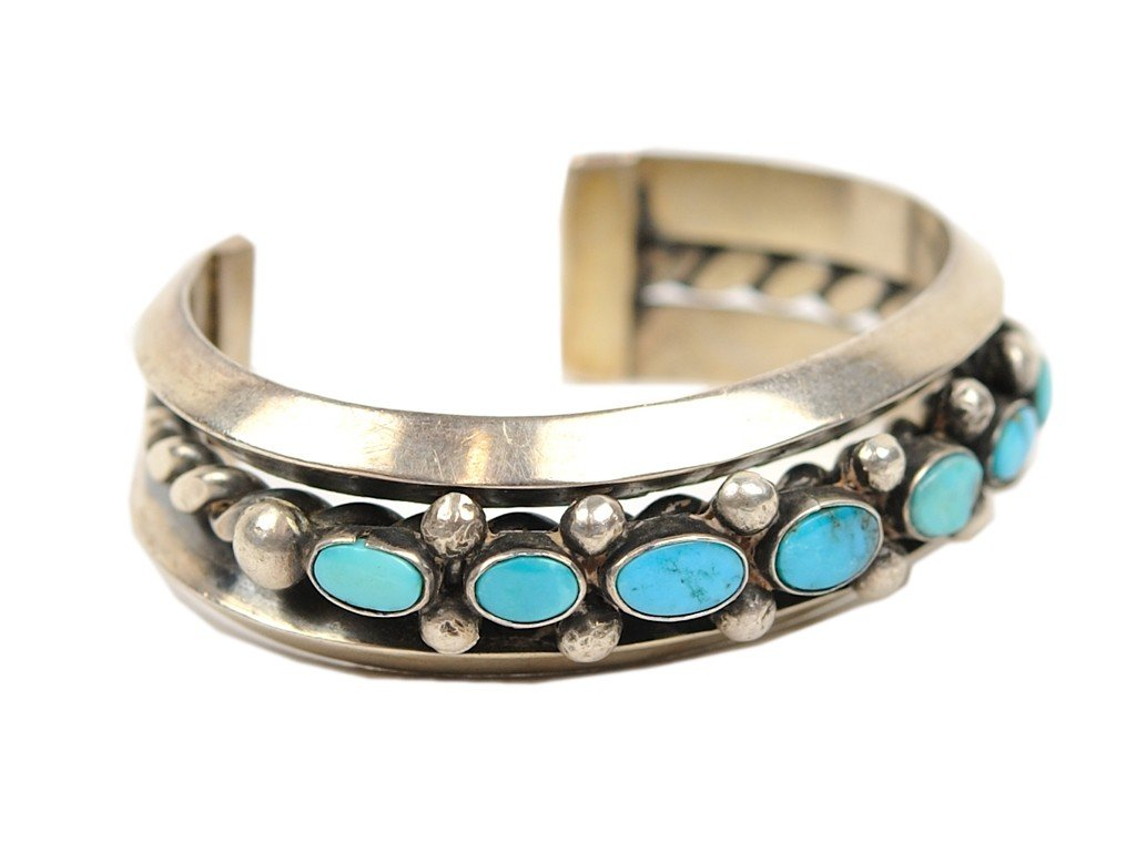 13: A SEVEN STONE TURQUOISE AND STERLING SILVER CUFF BR
