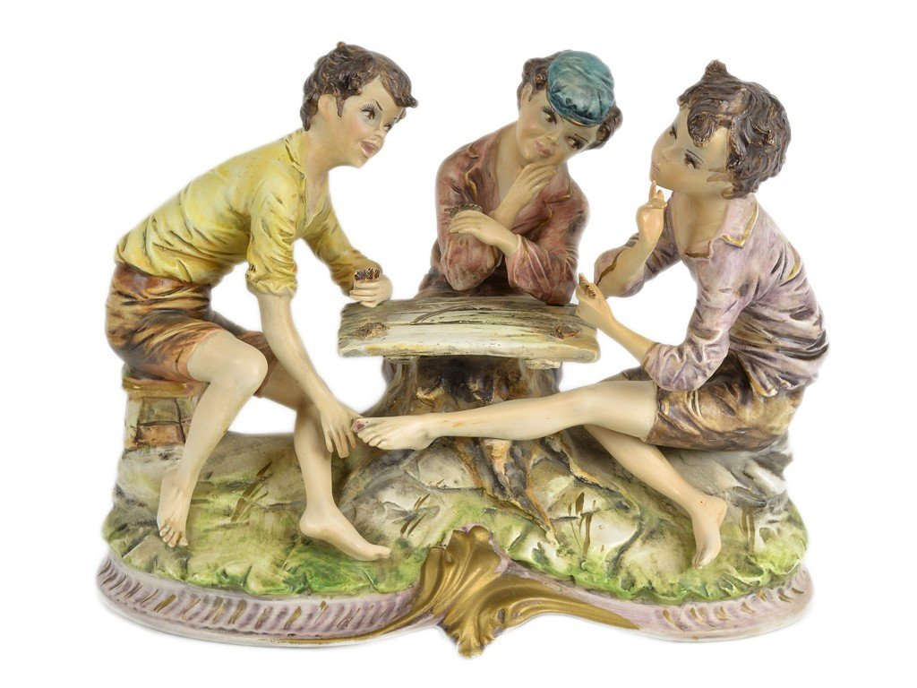 18: A VINTAGE ITALIAN BISQUE FIGURE OF THREE YOUNGSTERS