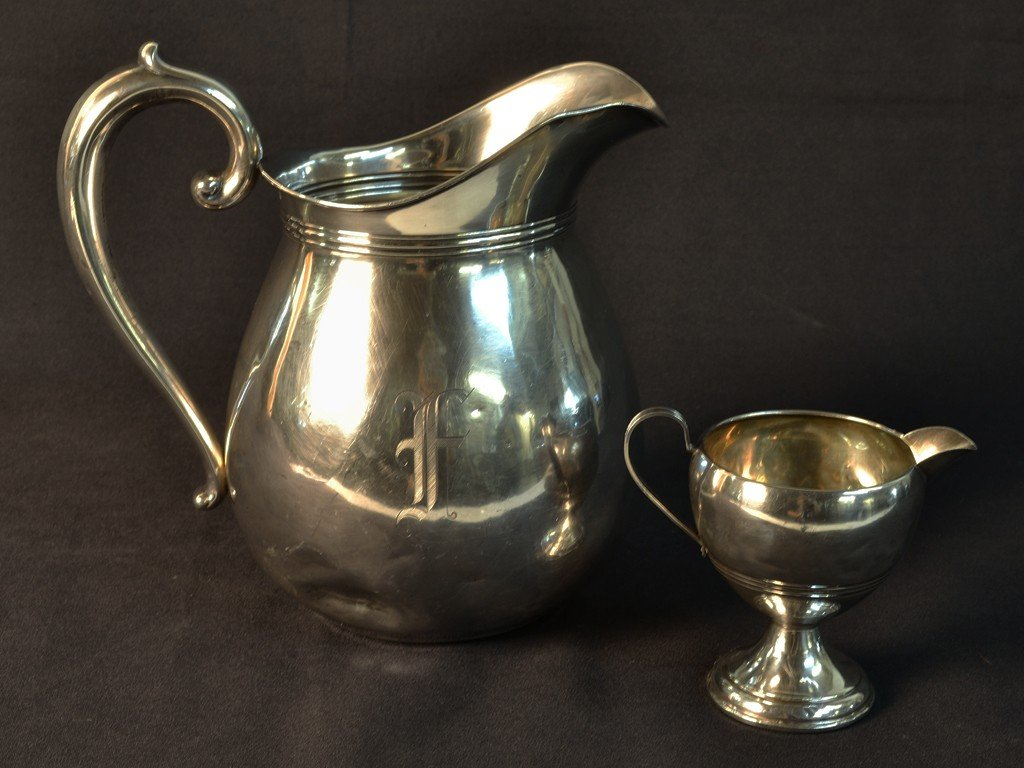 13: A STERLING SILVER WATER PITCHER AND CREAM PITCHER