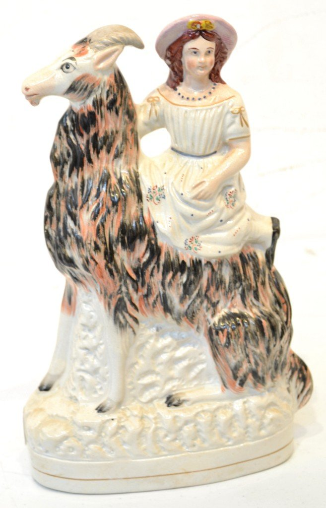17: AN ANTIQUE STAFFORDSHIRE FIGURE OF A YOUNG LADY ON
