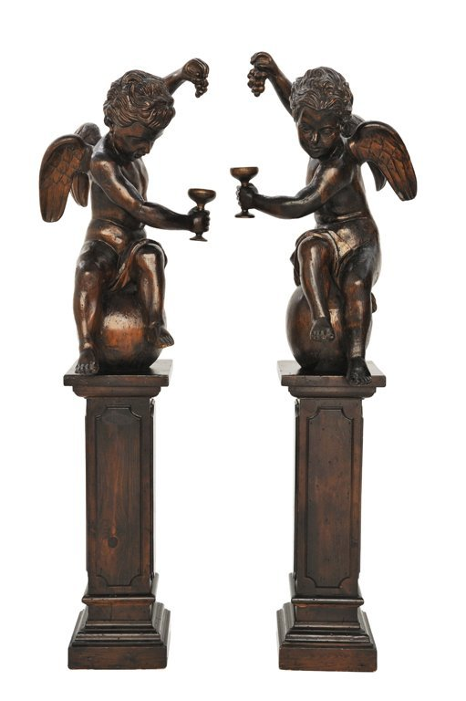 192: A GOOD PAIR OF HAND-CARVED EBONIZED CHERUBS ON PED