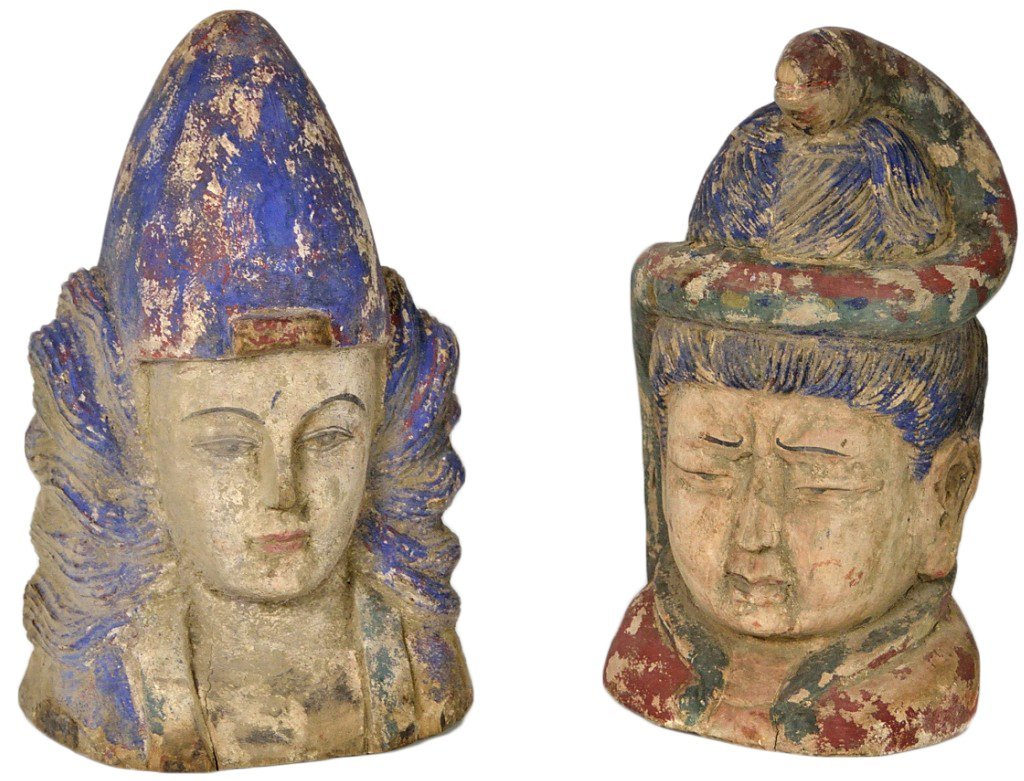 18: A PAIR OF CARVED ASIAN STYLE HEADS WITH ANTIQUED FI