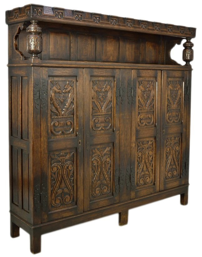 17: AN ANTIQUE HAND CARVED OAK BUFFET BOOKCASE