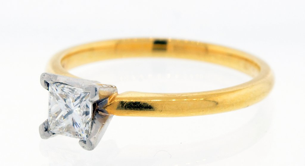 A LADIES 18KT PRINCESS CUT DIAMOND RING IN YELLOW AND W
