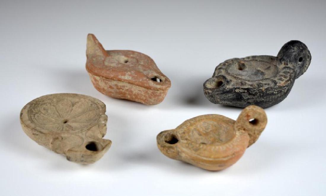 FOUR ANCIENT ROMAN OIL LAMPS