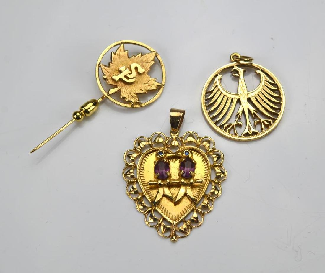 Two gold pendants and a gold commemorative pin