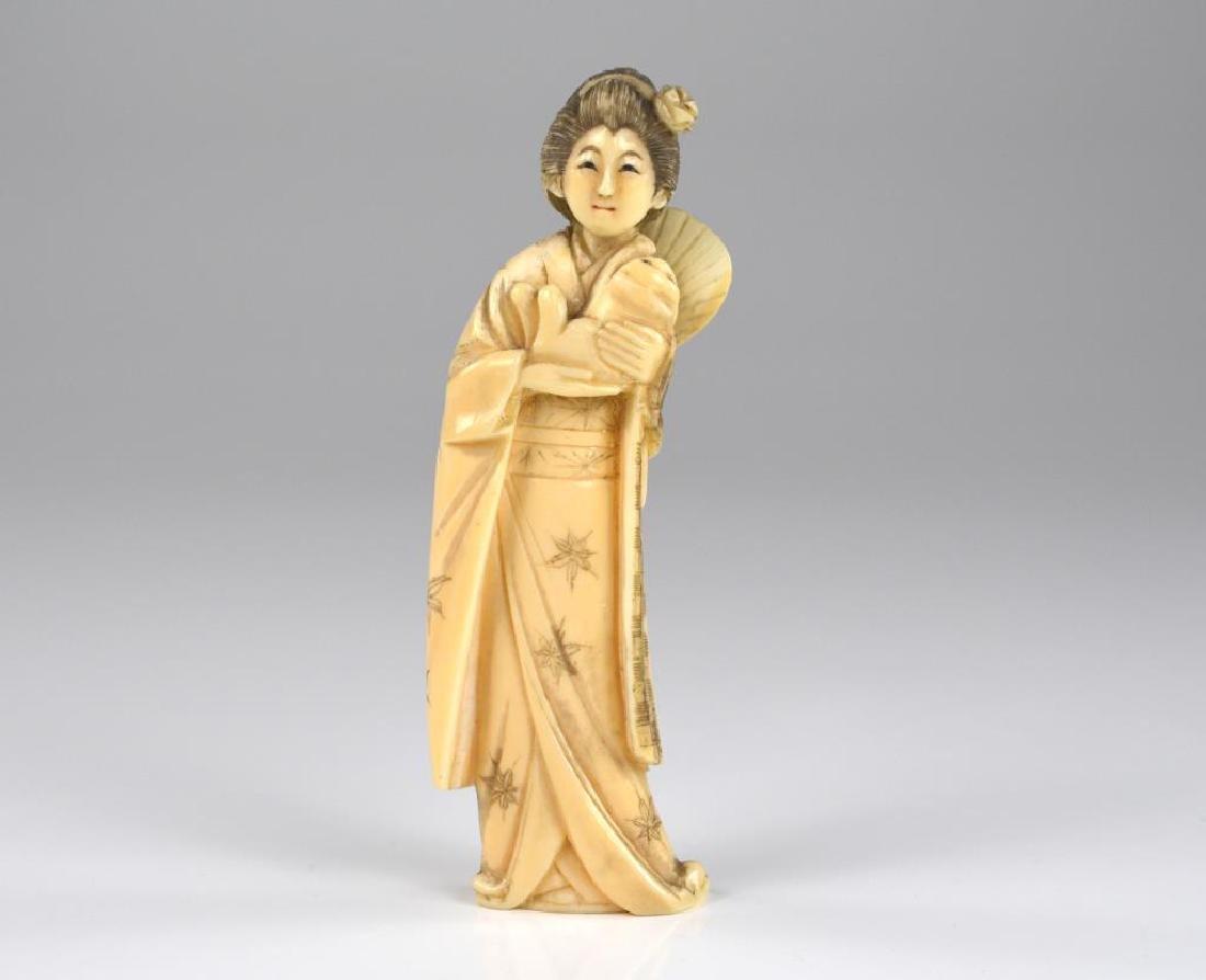 Japanese ivory okimono of a lady holding a puppy