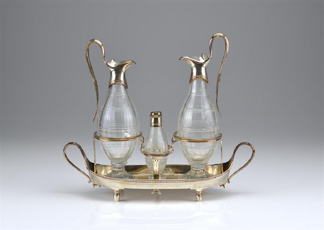 George III silver cruet stand with glass bottles