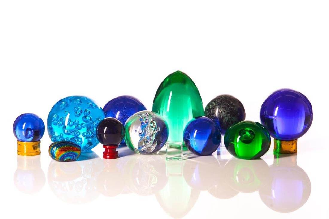 Assorted coloured glass paperweights and spheres