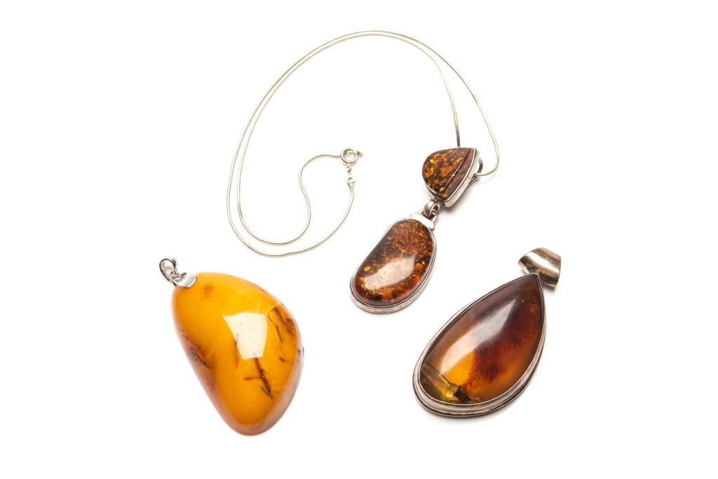 THREE NATURAL AMBER NECKLACE PENDANTS