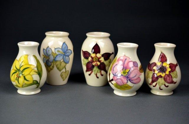 Five Moorcroft pottery vases on ivory ground