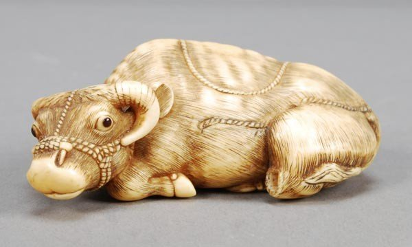 1: An ivory netsuke of a reclining ox, signed Tomotad