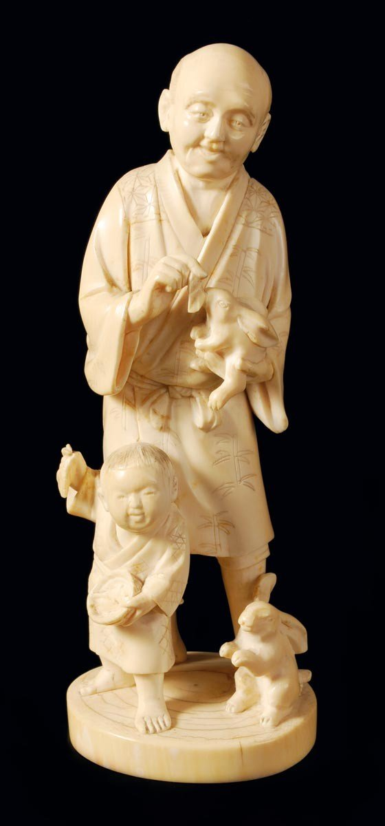 6: A Japanese ivory carving of a standing man holding