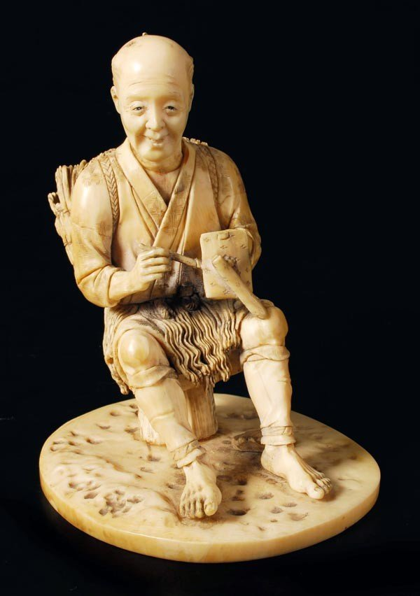 7: A Japanese ivory carving of a seated beachcomber f