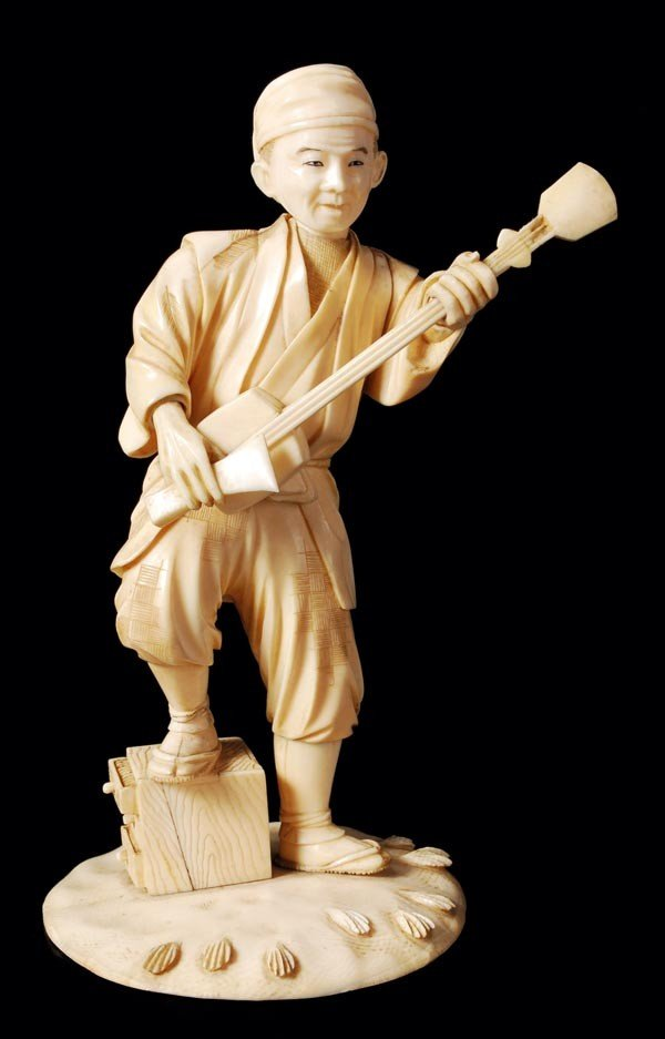17: A Japanese ivory figure of an itinerant musician,