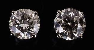 425: A pair of diamond single stone ear studs, the bril