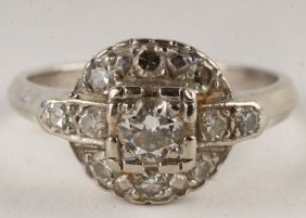 7: A diamond cluster ring, stamped '14K' to the white