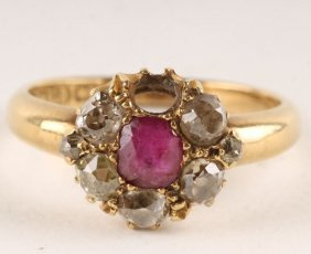 9: A ruby and diamond 18 carat gold cluster ring, the