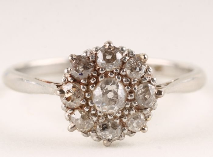 21: A nine stone diamond cluster ring, stamped 'Platin