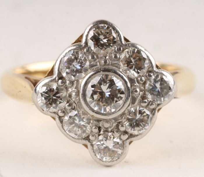 23: A nine stone diamond cluster ring, stamped '18ct &