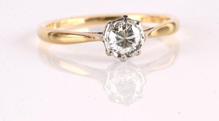 24: A diamond single stone 18 carat gold ring, the bri