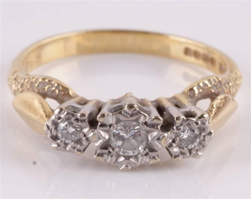 A diamond three stone 18 carat gold ring, the grad