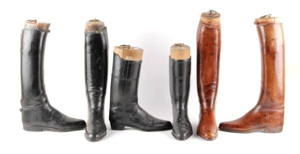 Two pairs of black leather riding boots,  the wood