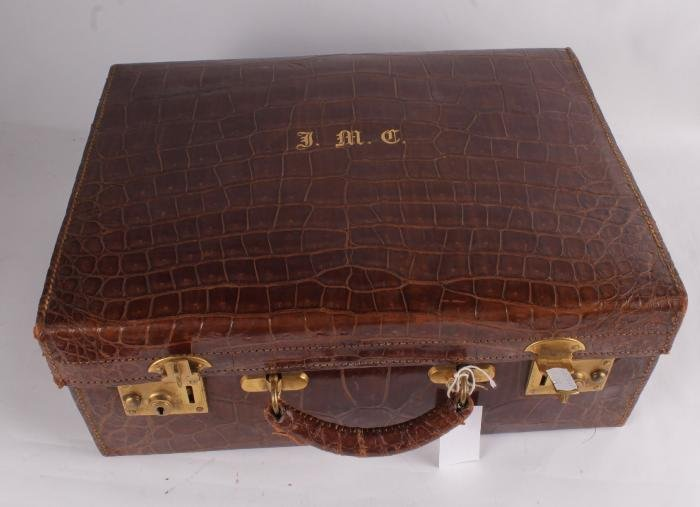 An early 20th century crocodile skin suitcase,  by