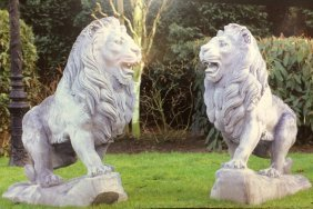 Pair of cast stone walking lions