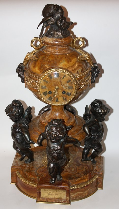 Marble clock with 4 cherubs holding a ball and bronze