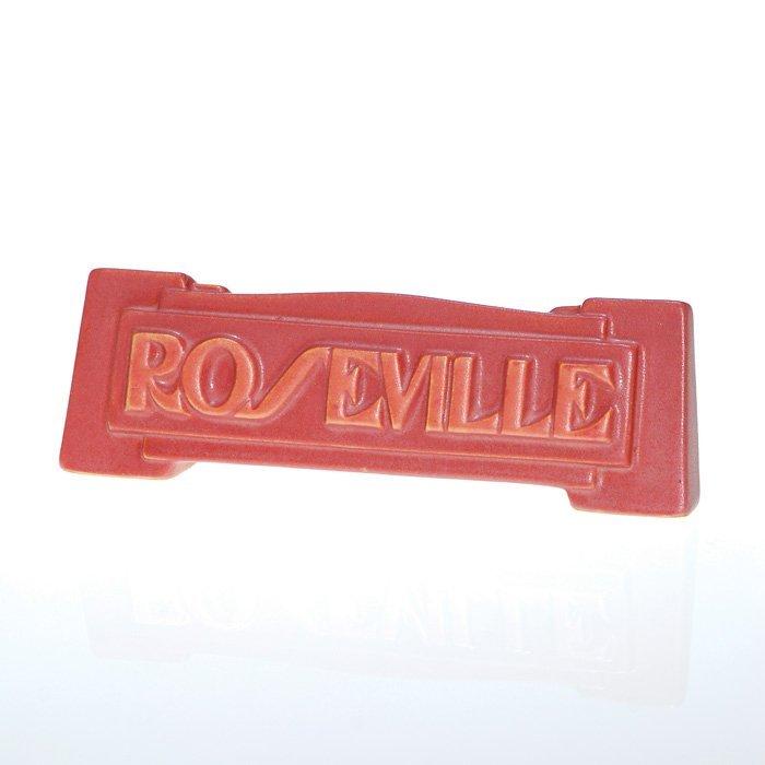 "0009: Roseville Art Deco 2"" X 6 1/4"" dealer sign."