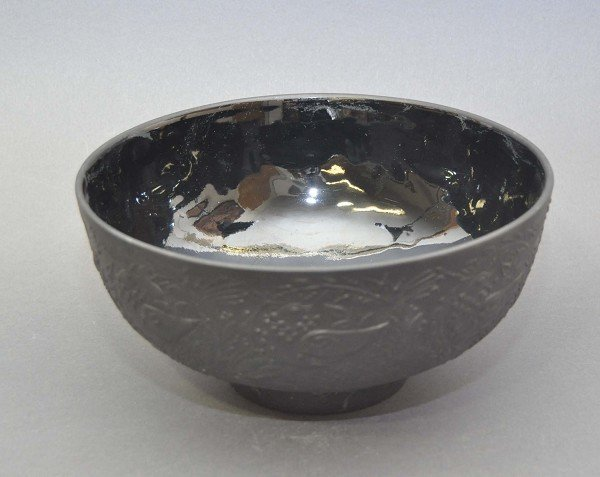 Black porcelain bowl, decorated in relief with bird and