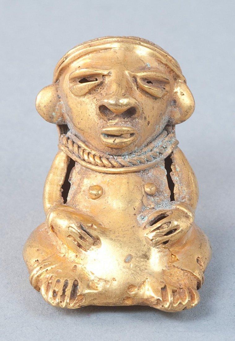 367: Tumbaga amulet, seated woman with necklace.Tairona