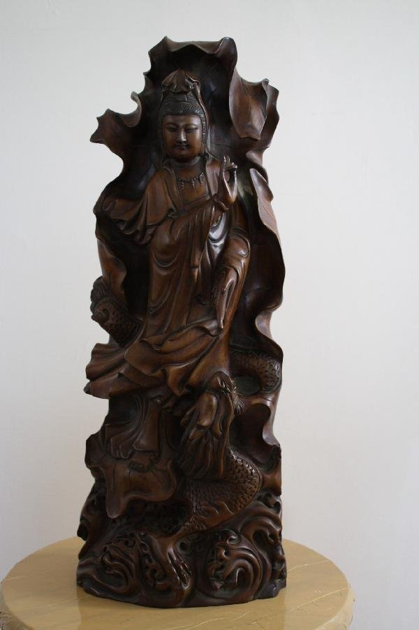 21: Hand carved boxwood figure of Guan Yin, sitting on