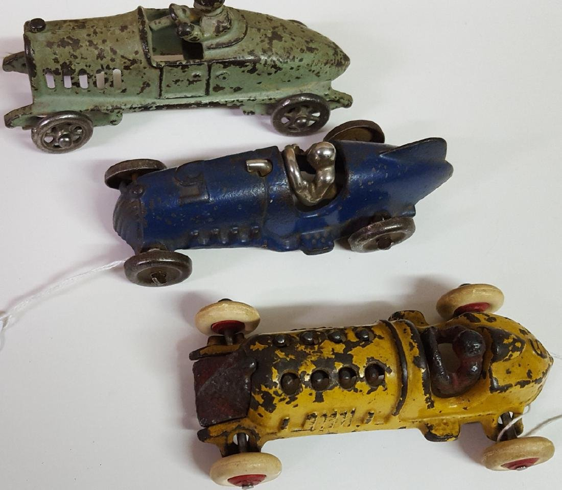 Three toy cast iron racers