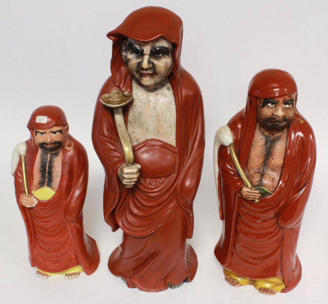THREE CHINESE IRON RED FIGURES OF LOHAN