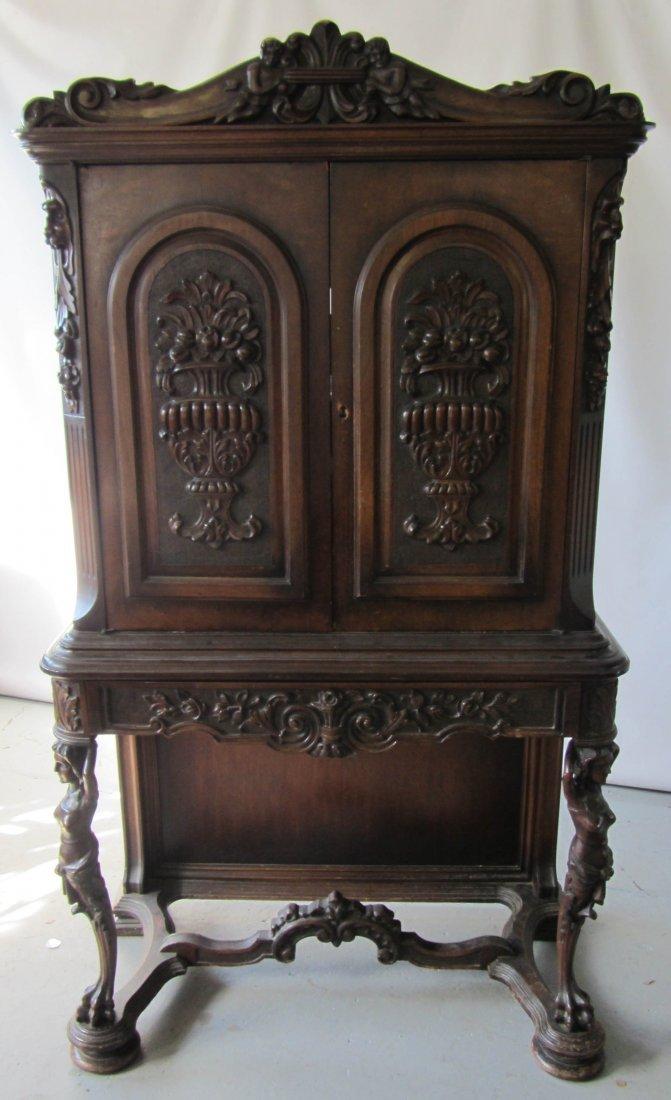 87: C1900 figural 2 door walnut cabinet