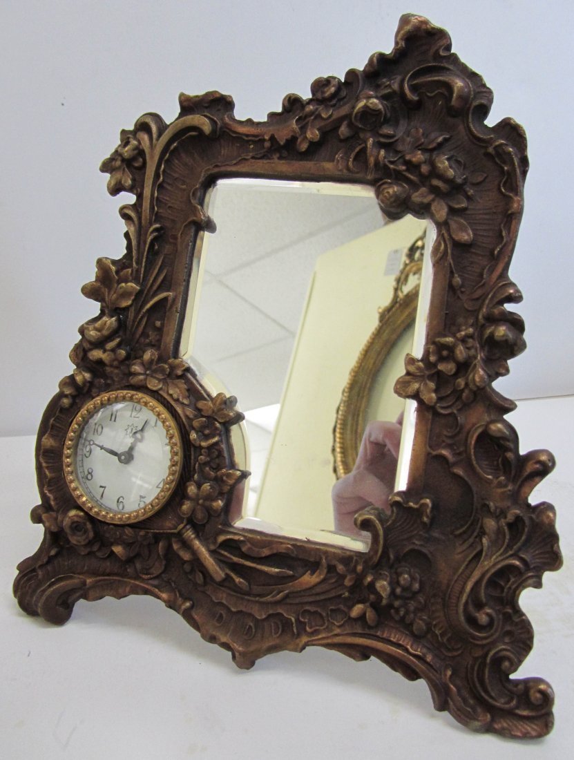 164: Bronze framed mirror with clock bevel glass