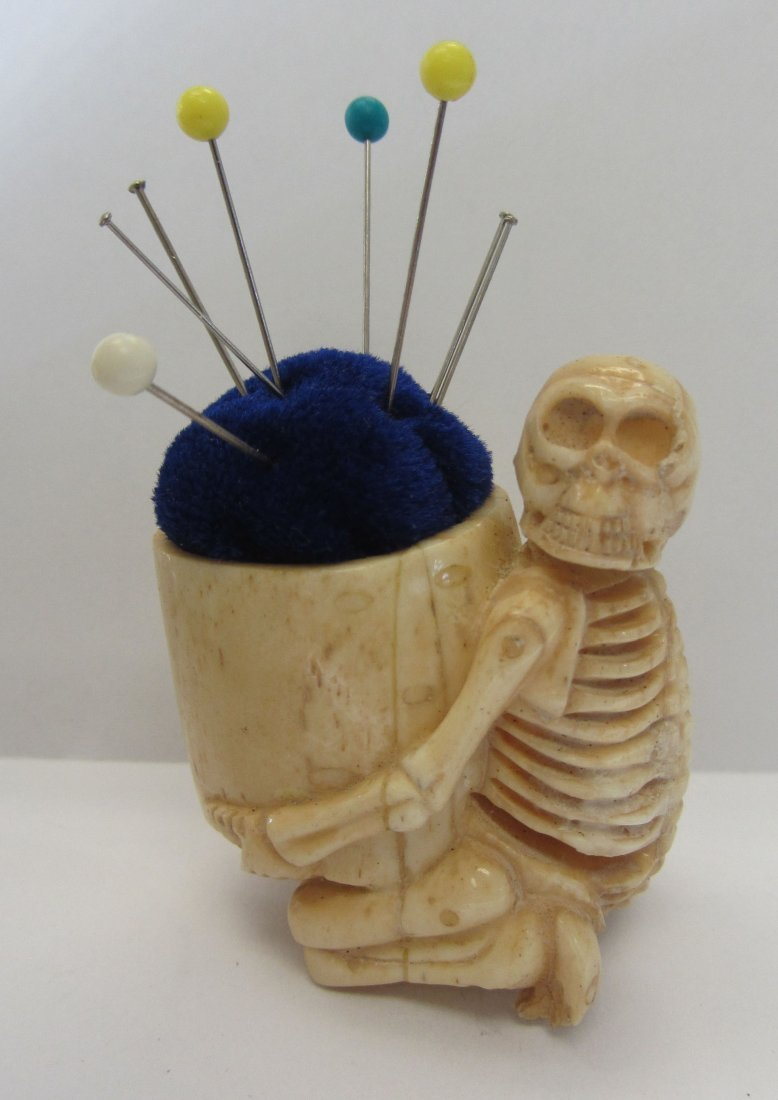 10: Carved bone skeleton pin cushion