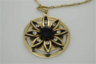 A vintage gold tone necklace with round pendant.