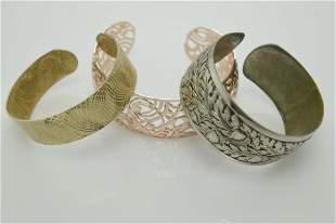 A lot of three silver tone cuffs.