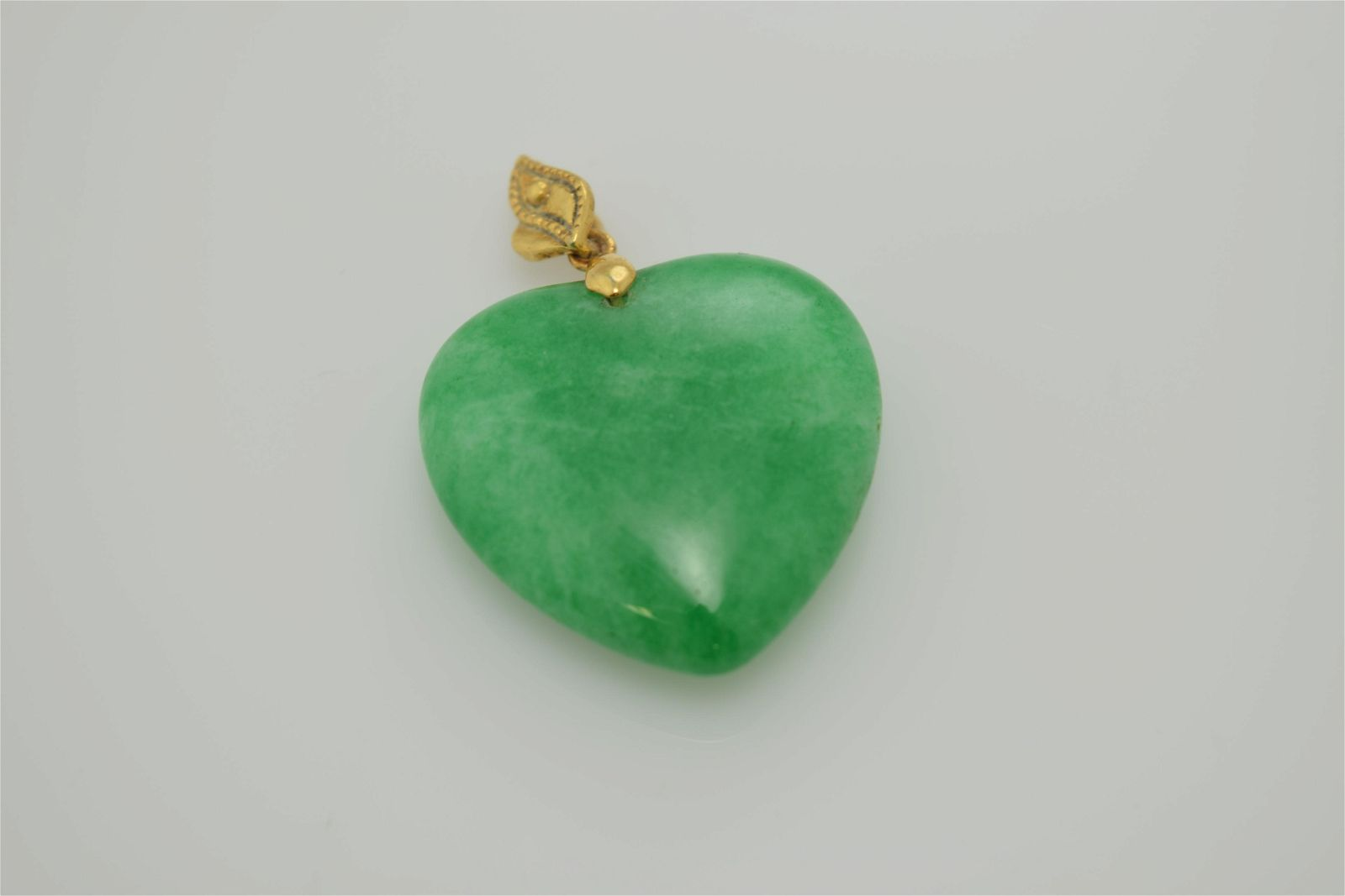 A modern jade (?) heart pendant.