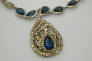 A modern silver tone necklace with blue and clear